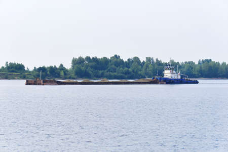 towboat pushes dry bulk cargo barge with sand on the river