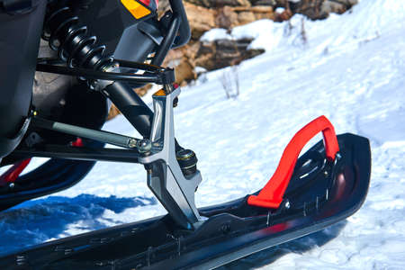 front ski of the snowmobile close up on blurred mountain winter landscape background