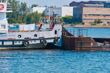 towboat pushes dry bulk cargo barge on the river close-up