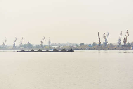 industrial river waterscape with dry bulk cargo barge and cargo terminal in morning fog