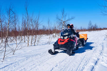 Russia, Perm Krai - March 28, 2021: people ride a snowmobile on a winter road among a birch forest-tundra