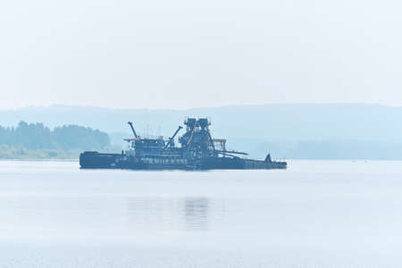 floating sand mining plant working on the river in the morning fog