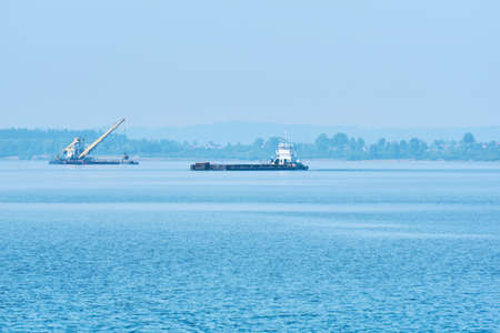 foggy river water landscape with cargo barge and grab dredge in the background 版權商用圖片