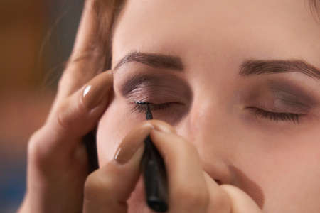 hands of a female make-up artist draw eyeliner on the eyelids of a woman model, close-up