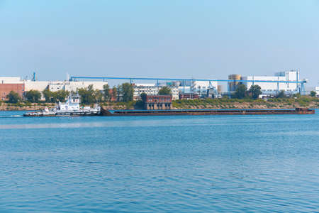 pusher boat pushes dry bulk cargo barge on the river against the backdrop of an industrial landscape on the shore 版權商用圖片