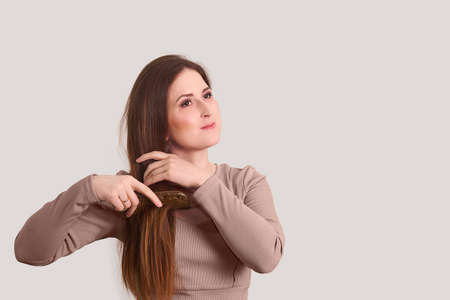 young beautiful woman combing her long straight hair with a comb on a light background 版權商用圖片