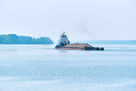 towboat pushes dry bulk cargo barge with sand on the river in the morning haze