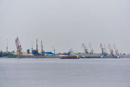 industrial river waterscape with timber cargo ship and cargo terminal