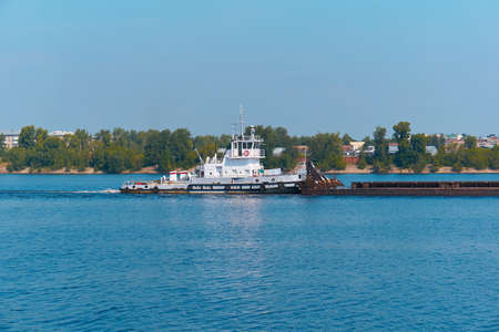 pusher boat pushes dry bulk cargo barge on the river past the city coast