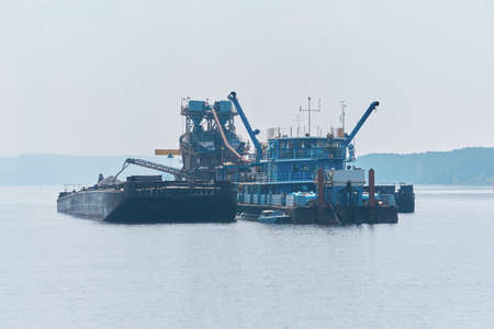 floating sand mining plant - dredger and separator - working on the river