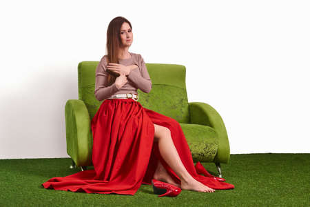 young attractive woman combing her hair while sitting on the couch in the studio and taking off her shoes while resting between shoots