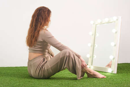woman looking at her reflection in illuminated mirror for dressing room sitting on floor in studio 版權商用圖片