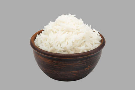 boiled white rice in simple clay bowl isolated on gray background