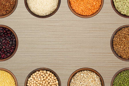 background - bowls with various cereals and legumes form a frame Archivio Fotografico