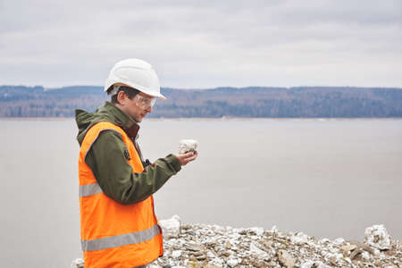 geologist or mining engineer examines a mineral sample from a talus on a river bank Archivio Fotografico