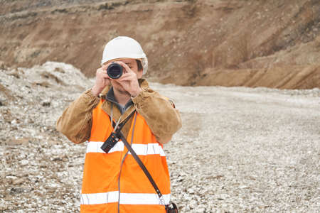 mining or road engineer using a spotting scope against the background of a mine Archivio Fotografico
