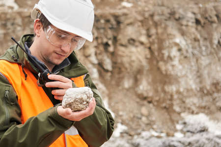 man geologist examines a mineral sample