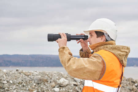 mining or road engineer using a telescope against the background of a riverbank quarry Archivio Fotografico