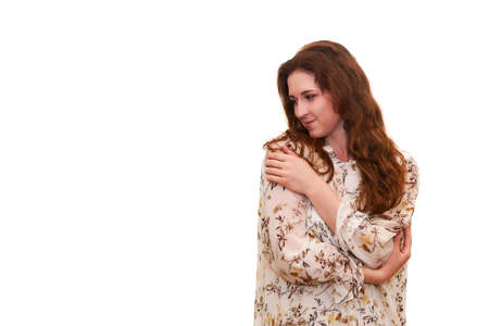 young attractive woman looks thoughtfully to the side, clasping herself with her arms, isolated on white background