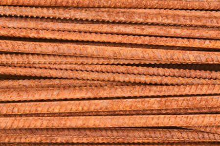 background - rusty reinforcing bars piled in a heap close-up