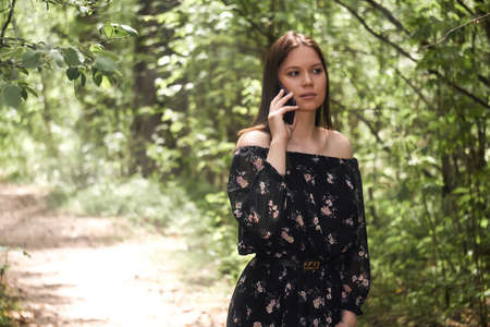beautiful girl talking on the phone walking in the sunny nature park