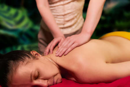 adult woman receives a back massage from a private massage therapist