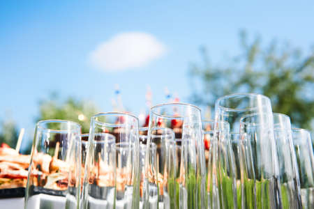 buffet in the open air - empty glasses on the background of cold snacks against the sky waiting for guests
