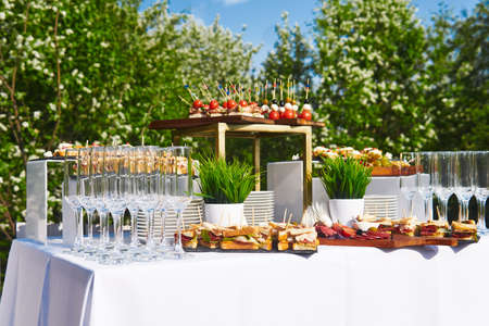 buffet in the open air - a table with canapes and glasses against the background of flowering trees and the sky