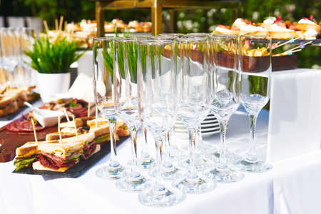 buffet in the open air - empty glasses on the background of cold snacks on the table waiting for guests