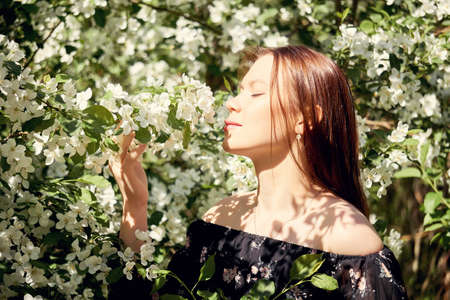 young woman inhales the scent of a blooming apple tree