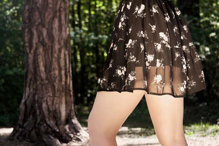 hips of a young woman walking in a forest park in a dress Archivio Fotografico