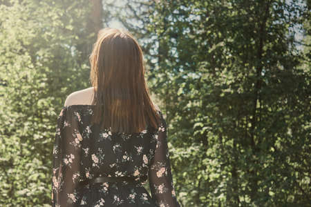 young woman in dress walking in the sunny nature park