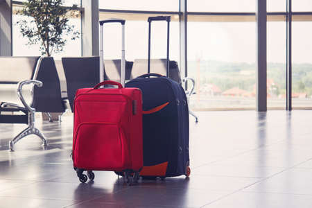 two suitcases are on the floor in airport lounge