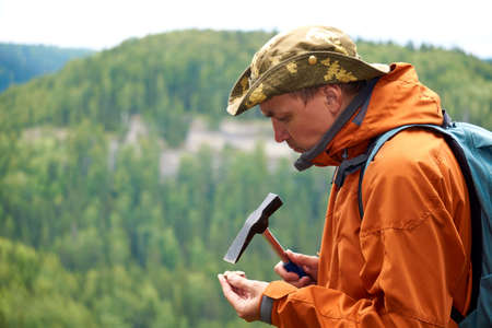 man geologist on an expedition examines a stone for hardness with a geological hammer