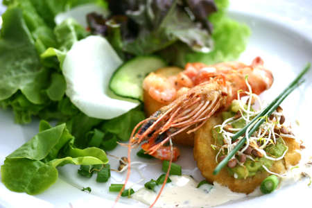 Starter plate containing prawns, shrimps, sprouts and onions on a bed of lettuce