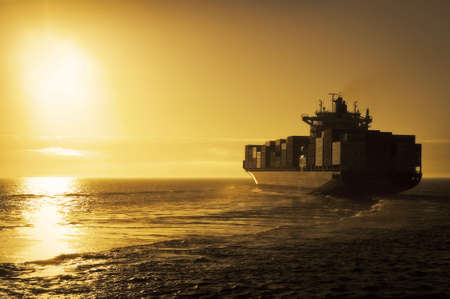 loading cargo: Cargo container ship sailing off into the sunset Stock Photo