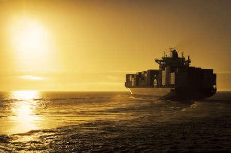 containerschip: Vracht container schip zeilen uit in de zons ondergang