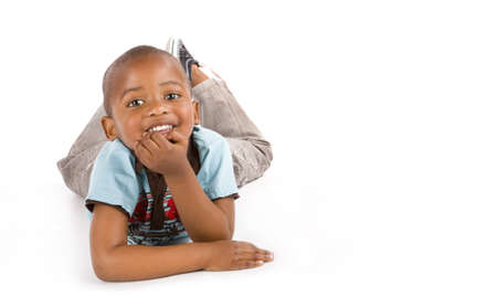 Adorable 3 year old black or African American boy with a big smile laying on the floor, space for your text.