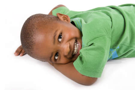 Adorable 3 year old black or African American boy with a smile laying on the floor looking at you