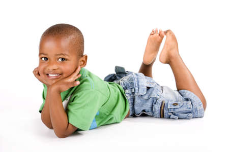 Adorable 3 year old black or African American boy with a big smile laying on the floor with his feet up looking at you