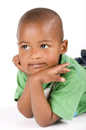 Adorable 3 year old black or African American boy laying on the floor staring into space