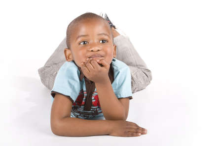 african american infant: Adorable 3 year old black or African American boy lying with his left hand on his chin