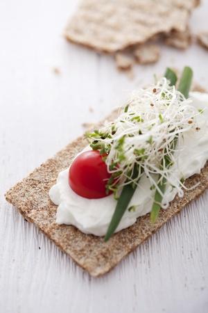 broccoli sprouts: crisp bread sandwich with cream cheese, broccoli sprouts, tomato and chive