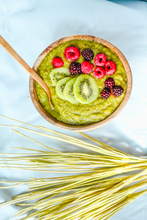 kiwis: Green smoothies with spirulina bowl, pears, kiwis and berries, raw breakfast, wooden tableware,light background Stock Photo