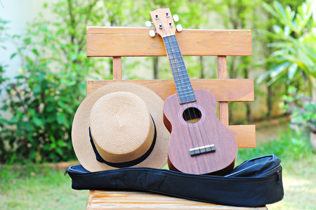 Brown Ukulele with lovely hat placed on a wooden chair