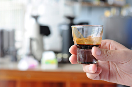 hand with hot coffee ristretto in glass