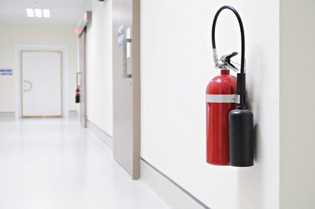 Install a fire extinguisher on the wall in hospital photo