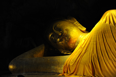 nirvana: smile reclining buddha statue in nirvana position at Cave, Phetchaburi, Thailand
