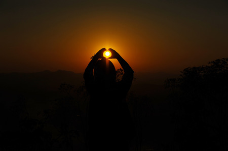 human's arm: Woman Hands made heart shape at sunset Stock Photo