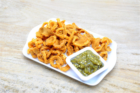 rinds: Pork rinds  with Chilis at the plate on wooden background